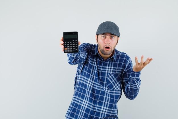 Junger mann, der taschenrechner im hemd, in der kappe zeigt und ratlos schaut. vorderansicht.