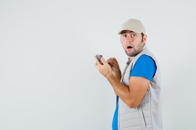 Junger mann, der taschenrechner im t-shirt, in der jacke benutzt und verwirrt schaut. .