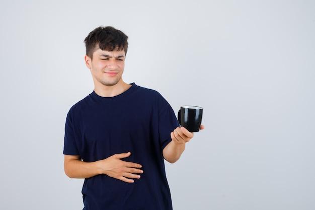 Junger mann, der tasse im schwarzen t-shirt betrachtet und unzufrieden schaut, vorderansicht.