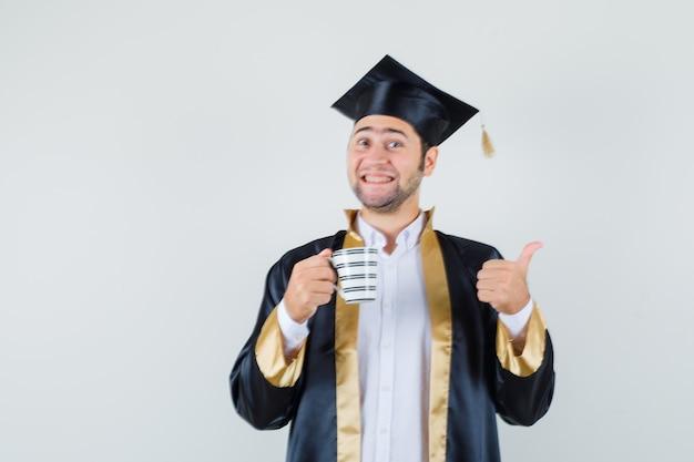 Junger mann, der tasse kaffee hält, daumen oben in der abschlussuniform zeigt und fröhlich, vorderansicht schaut.