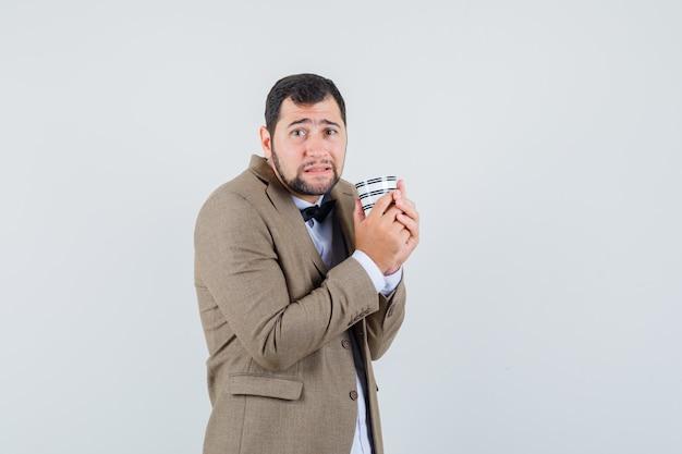 Junger mann, der tasse kaffee im anzug hält und bescheiden, vorderansicht schaut.