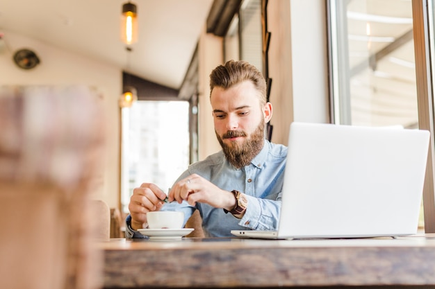 Junger mann, der tasse kaffee mit laptop auf schreibtisch hat