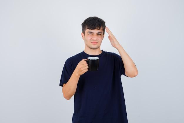 Junger mann, der tasse tee hält, hand im schwarzen t-shirt erhebt und verwirrt, vorderansicht schaut.