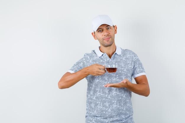 Junger mann, der tasse tee im t-shirt und in der mütze hält und fröhlich schaut