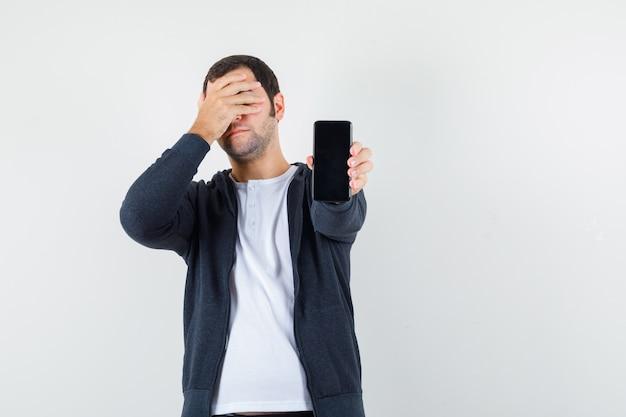 Junger mann, der telefon hält und auge mit einer hand im weißen t-shirt und im schwarzen kapuzenpullover mit reißverschluss vorne abdeckt und genervte vorderansicht schaut.
