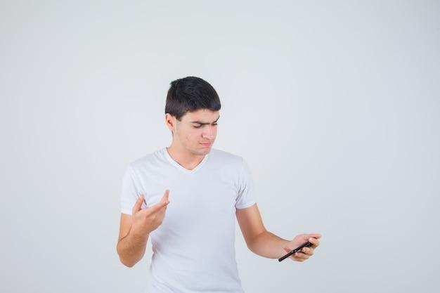 Junger mann, der telefon hält, während er im t-shirt beiseite zeigt und konzentriert schaut. vorderansicht.