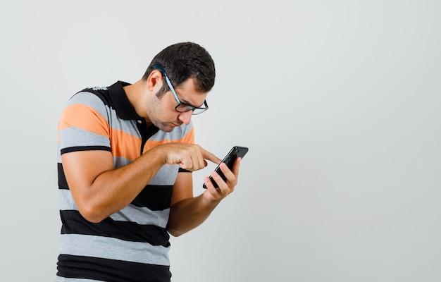 Junger mann, der telefon in t-shirt, brille betrachtet und vorsichtig schaut. platz für text