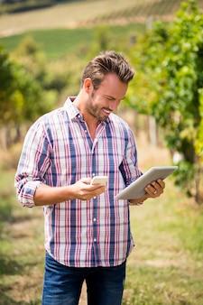 Junger mann, der telefon und tablette am weinberg verwendet