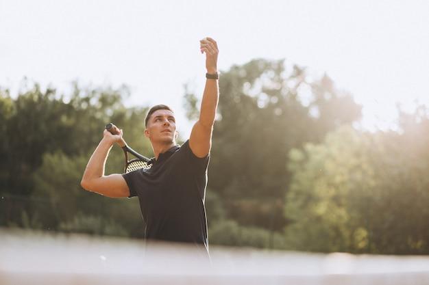 Junger mann, der tennis am gericht spielt