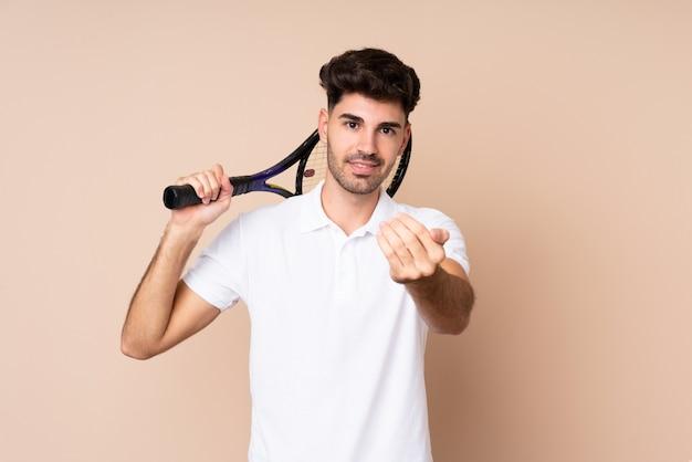 Junger mann, der tennis spielt und kommende geste tut
