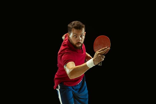 Junger mann, der tischtennis auf schwarz spielt