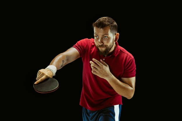 Junger mann, der tischtennis auf schwarzem studio spielt