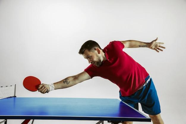 Junger mann, der tischtennis auf weißer studiowand spielt
