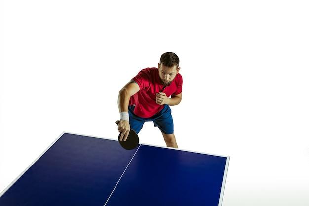 Junger mann, der tischtennis auf weißer wand spielt