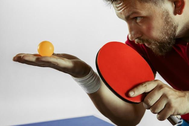 Junger mann, der tischtennis spielt