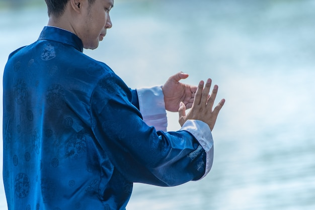 Junger mann, der traditionelles tai chi chuan, tai ji und qi-gong, chinesische kampfkünste übt.