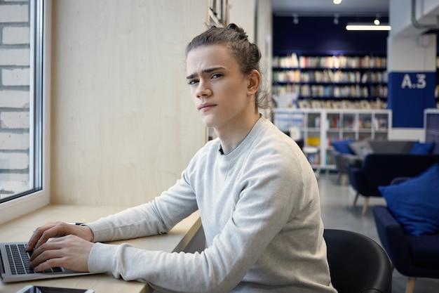 Junger mann, der tragbares notizbuch im café benutzt, am tisch am fenster sitzt und etwas tippt und die stirn runzelt