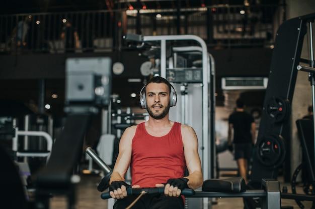 Junger mann, der training auf einer rückseite mit energieübungsmaschine in einem turnhallenclub tut