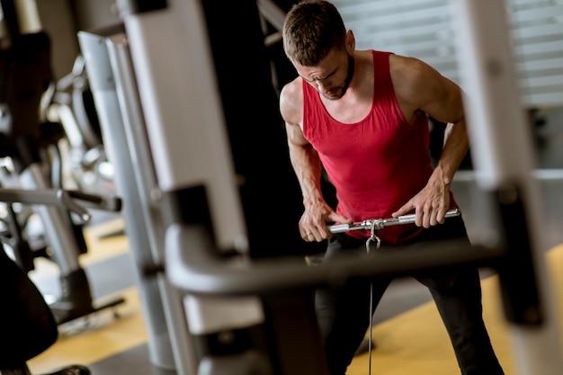 Junger mann, der training für eine rückseite mit energieübungsmaschine in einem turnhallenclub tut