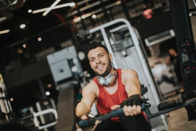 Junger mann, der trainingseinheiten auf einer rückseite mit kraftübungsmaschine in einem turnhallenverein tut