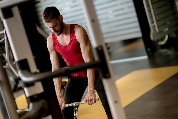Junger mann, der trainingseinheiten für eine rückseite mit kraftübungsmaschine in einem turnhallenverein tut