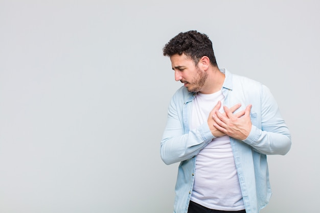 Junger mann, der traurig, verletzt und mit gebrochenem herzen aussieht, beide hände nah am herzen hält, weint und sich deprimiert fühlt