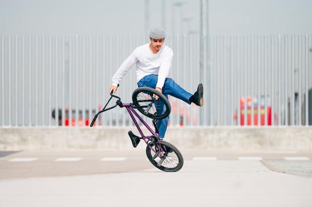 Junger mann, der tricks mit einem flachland-bmx-fahrrad durchführt