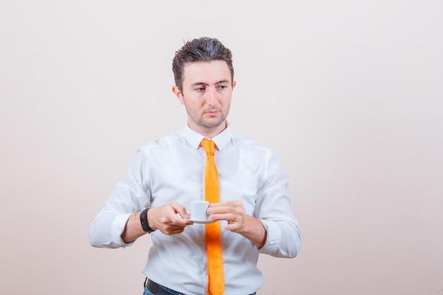 Junger mann, der türkischen kaffee in weißem hemd, krawatte trinkt und nachdenklich aussieht