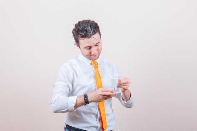 Junger mann, der türkischen kaffee in weißem hemd, krawatte trinkt und vorsichtig aussieht