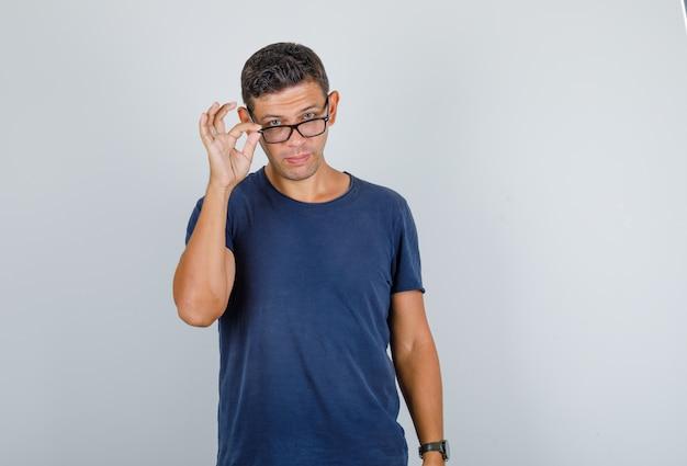 Junger mann, der über brille im dunkelblauen t-shirt, vorderansicht späht.