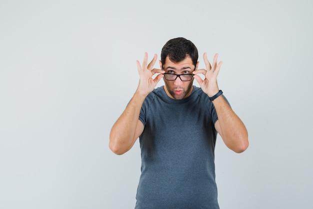 Junger mann, der über brille im grauen t-shirt schaut und überrascht, vorderansicht schaut.