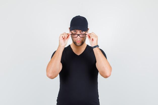 Junger mann, der über brille im schwarzen t-shirt, mütze schaut und überrascht schaut.