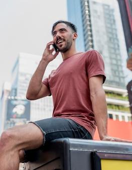 Junger mann, der über telefon sitzt und spricht
