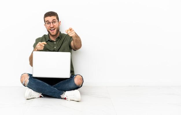 Junger mann, der überrascht auf dem boden sitzt und nach vorne zeigt