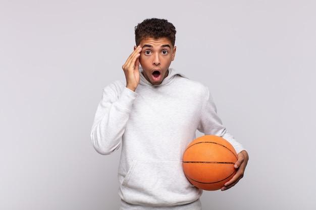 Junger mann, der überrascht, mit offenem mund, schockiert aussieht und einen neuen gedanken, eine neue idee oder ein neues konzept realisiert. korbkonzept