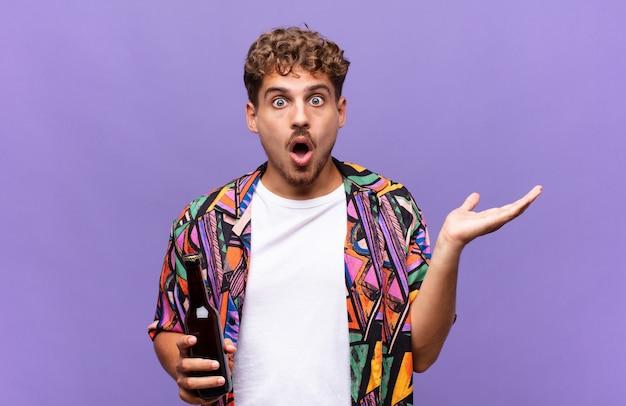 Junger mann, der überrascht und schockiert aussieht, mit gesenktem kiefer, der einen gegenstand mit einer offenen hand auf der seite hält