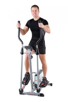 Junger mann, der übungen auf elliptischem trainer tut
