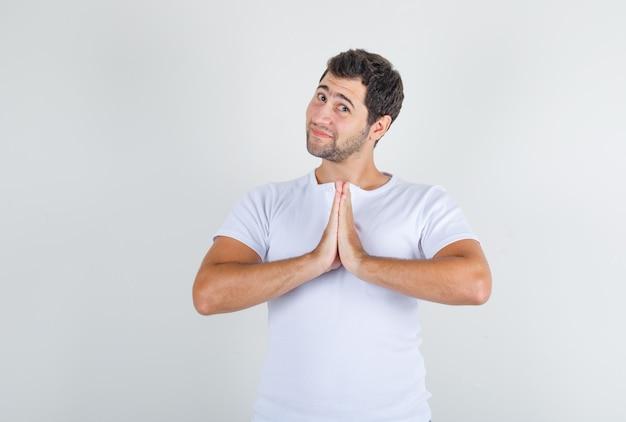 Junger mann, der um vergebung bittet, während er im weißen t-shirt lächelt und hoffnungsvoll aussieht