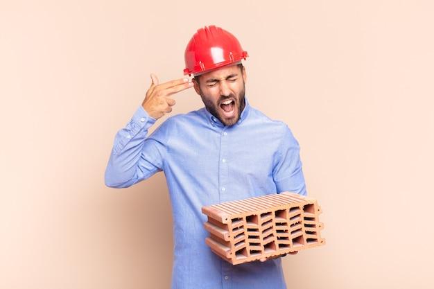 Junger mann, der unglücklich und gestresst aussieht, selbstmordgeste, die waffenzeichen mit der hand macht und auf den kopf zeigt. architektenkonzept
