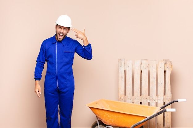 Junger mann, der unglücklich und gestresst schaut, selbstmordgeste, die waffenzeichen mit hand macht, zeigt auf kopfkonstruktionskonzept