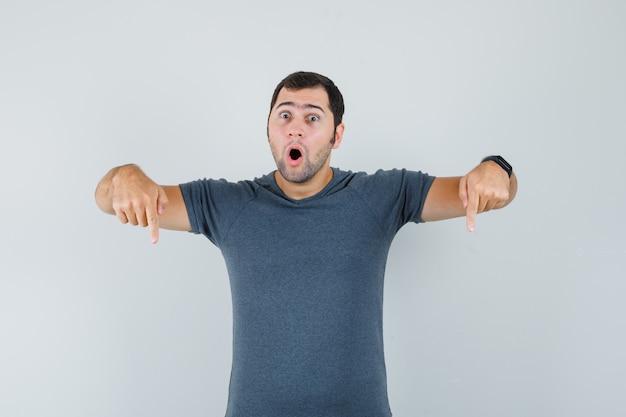 Junger mann, der unten im grauen t-shirt zeigt und erstaunt, vorderansicht schaut.