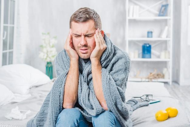 Junger mann, der unter erkältung kopfschmerzen hat
