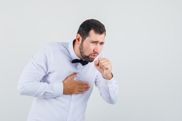 Junger mann, der unter husten im weißen hemd leidet und krank aussieht. vorderansicht.