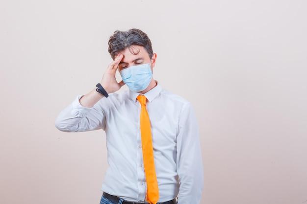 Junger mann, der unter kopfschmerzen in hemd, krawatte, jeans, maske leidet und erschöpft aussieht
