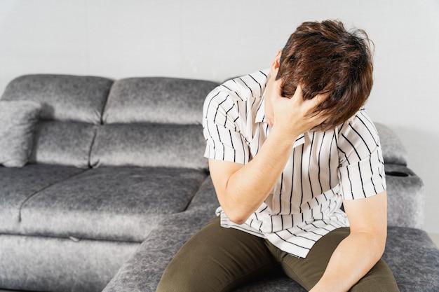 Junger mann, der unter kopfschmerzen leidet