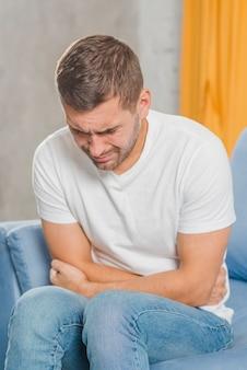 Junger mann, der unter magenschmerzen leidet
