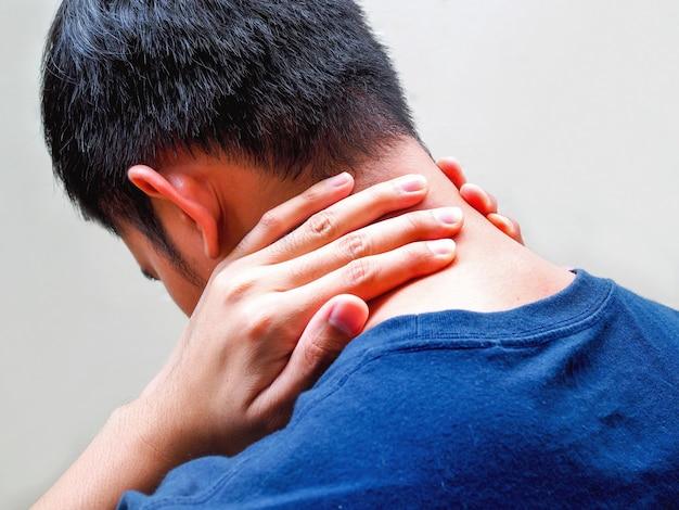 Junger mann, der unter nackenschmerzen, starken rücken- und schulterschmerzen leidet.