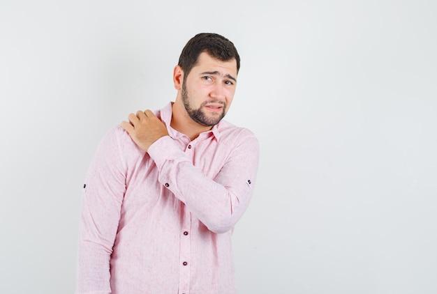 Junger mann, der unter schulterschmerzen im rosa hemd leidet und müde schaut