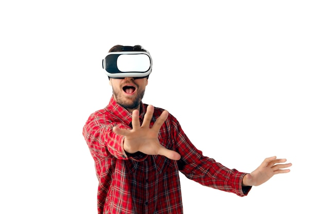 Junger mann, der unter verwendung der virtuellen realität headset lokalisiert auf weißer studiowand spielt