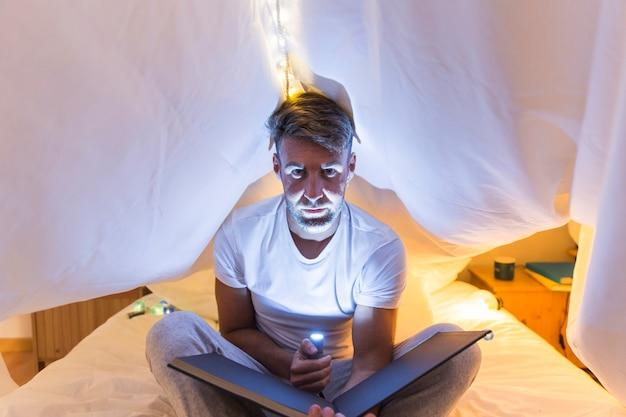 Junger mann, der unter vorhang auf bettblitztaschenlampe über dem gesicht hält fotoalbum sitzt